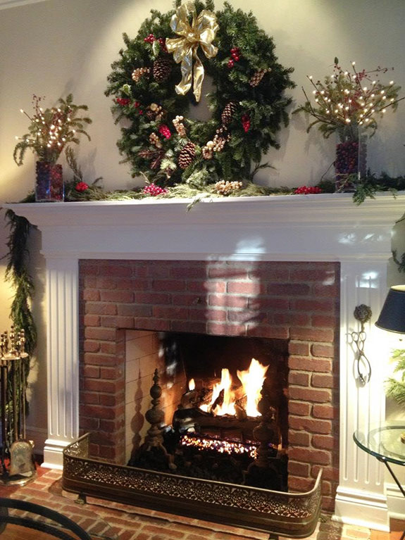 mantel decorated in classic christmas style with wreath, pine cones, pillar candles, and ribbon