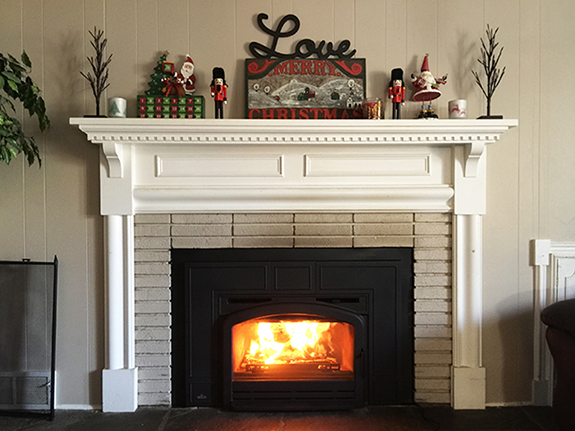 mantel decorated in a whimsical style with vibrant nutcracker and santa figurines, a present, a sign, and small trees
