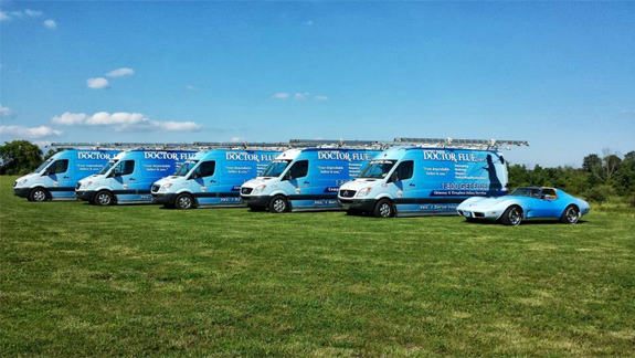 the entire doctor flue inc fleet with 5 blue vans and one blue corvette lined up together