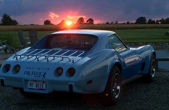 doctor flue inc's blue corvette facing a setting sun