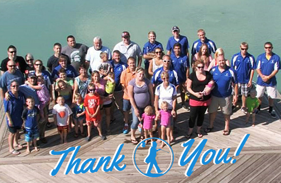 employees of doctor flue, inc. and their families standing together on a deck with water in the background