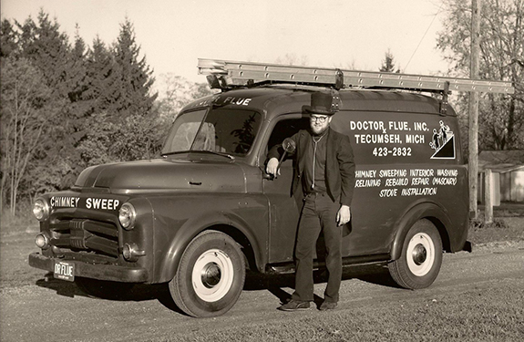 doctor flue dressed in traditional chimney sweep attire, leaning on the driver's side door of his first truck, a 1953 dodge panel