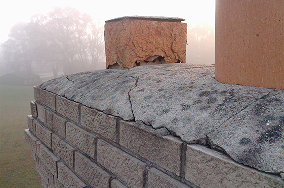 Close up of a deteriorating brick chimney with a foggy background.
