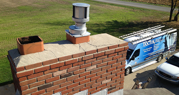A cracked chimney crown viewed from a rooftop with a Doctor Flue truck parked in the driveway behind it, ready to make chimney masonry repair.