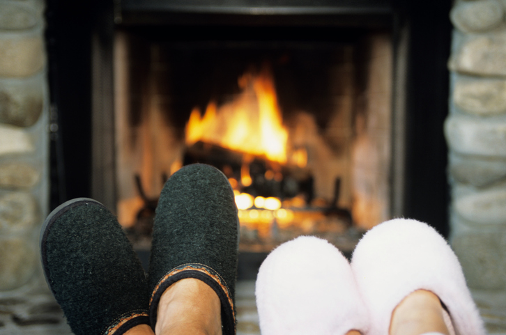 Two pairs of feet with slippers on in front of fireplace
