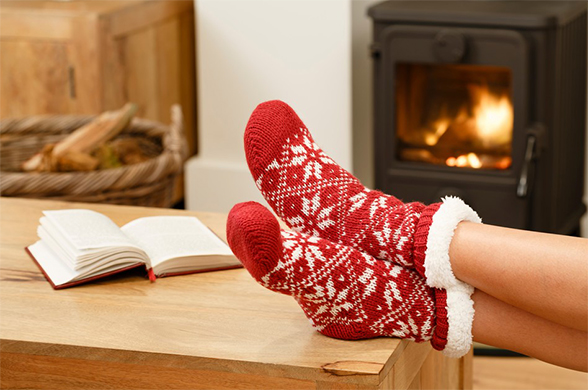A person's feet in red-and-white knitted slippers, propped up on a table in front of a book and a wood stove.