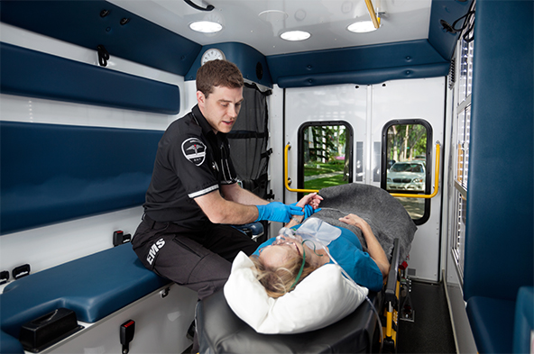 EMT in an ambulance takes the pulse of a woman who is lying on a stretcher and breathing through an oxygen mask.