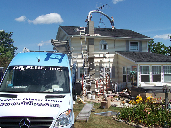 Doctor Flue installing a new chimney liner on the roof of a home with the Doctor Flue sprinter van in the foreground.