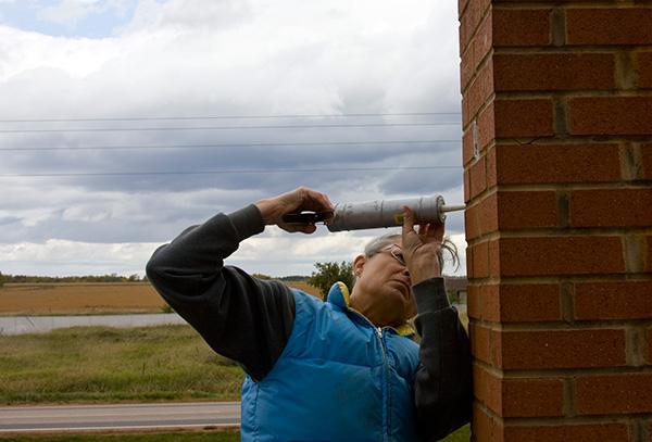Woman repairing a brick chimney with caulk.