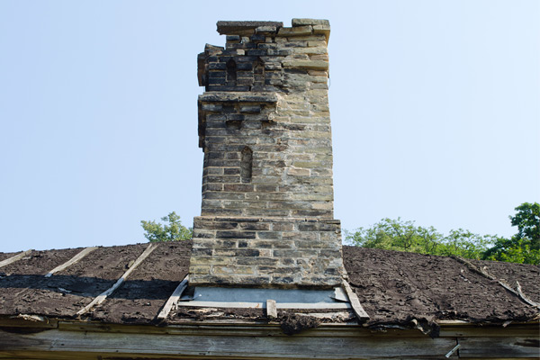 A damaged chimney with missing bricks and scorch marks on a damaged roof due to chimney fire.