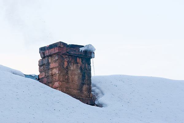 Scorched brick chimney on snow covered rooftop.