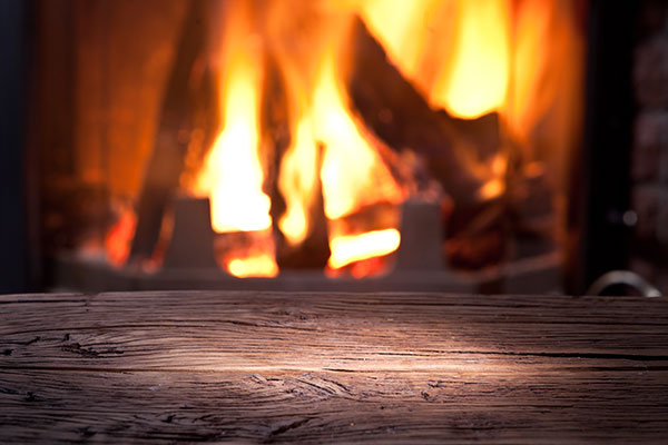 View of a fireplace over an old wooden table.