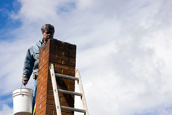 A man standing at his chimney looking for common fireplace problems.
