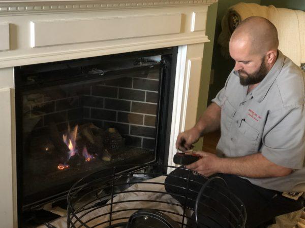 Kevon Binder of Doctor Flue servicing a customer's gas fireplace.