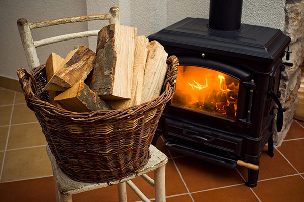 A fire burns brightly in a wood stove and a basket with additional firewood sits on a nearby chair.