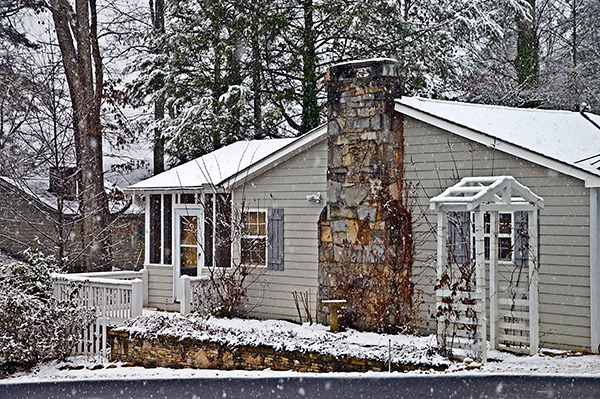 Snowfall on a house with a large stone chimney means it's time for winter chimney prep.