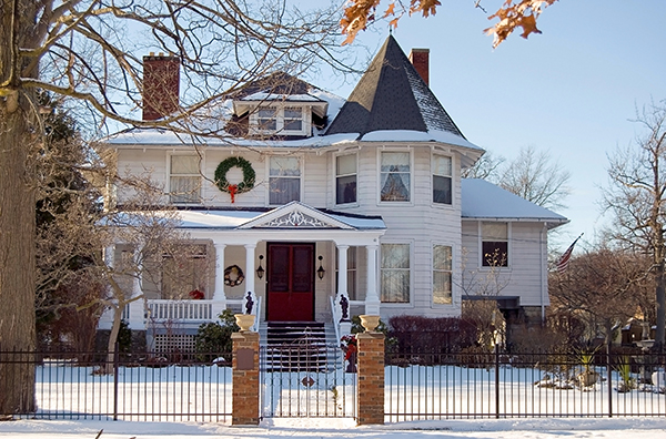 A stately Victorian home is dusted with snow at Christmastime. These historic homes can be plagued with old chimney problems