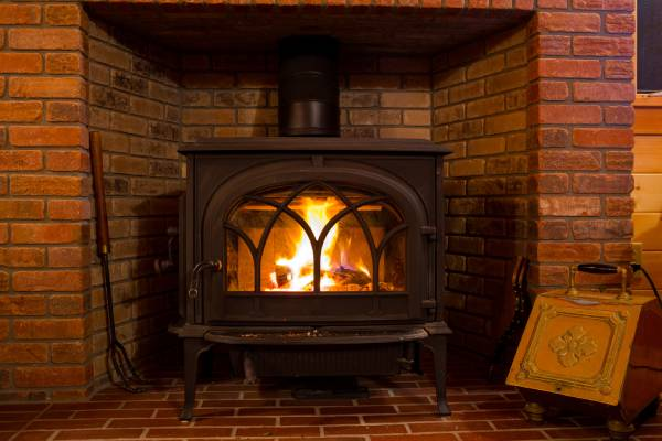 A fire burns brightly inside a wood stove. Heating efficiency for your whole home can be improved with wood stove heating.