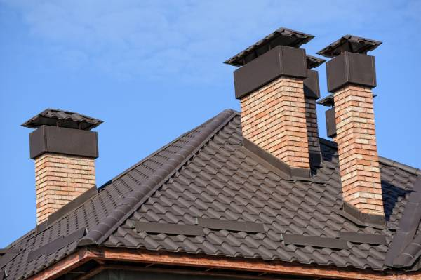 Multiple chimneys on this roof all have chimney covers. Chimney protection is important to keep your chimney and home safe.